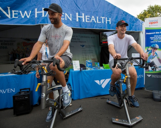 August 21, 2014, New Haven, CT: James Blake and Andy Roddick ride spin bikes for Yale New Haven Health during the Men's Legends Event on day seven of the 2014 Connecticut Open at the Yale University Tennis Center in New Haven, Connecticut Thursday, August 21, 2014. (Photo by Billie Weiss/Connecticut Open)